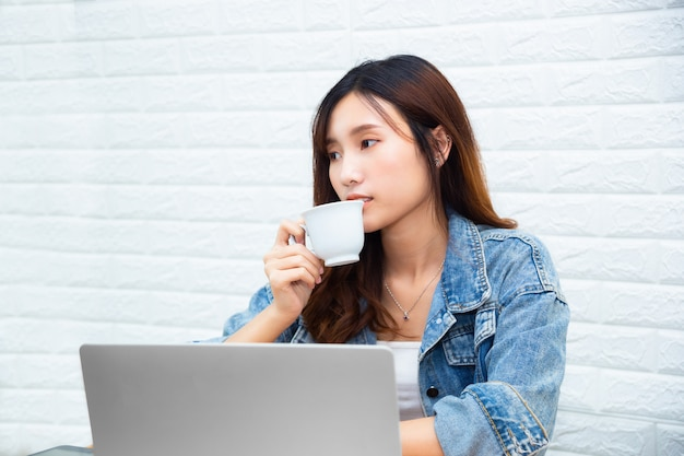Young working woman drinking coffee at office