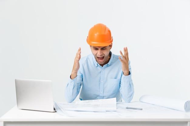 Giovane operaio infastidito arrabbiato nel gesto furioso. espressione negativa su sfondo grigio bianco.