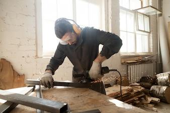 Young workman grinding steel metal profile pipe in workshop interior