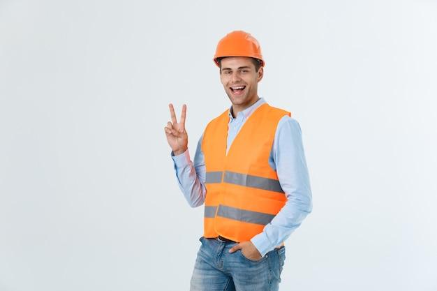 幸せなヘルメットと緑の背景に指で2を数える若い職人