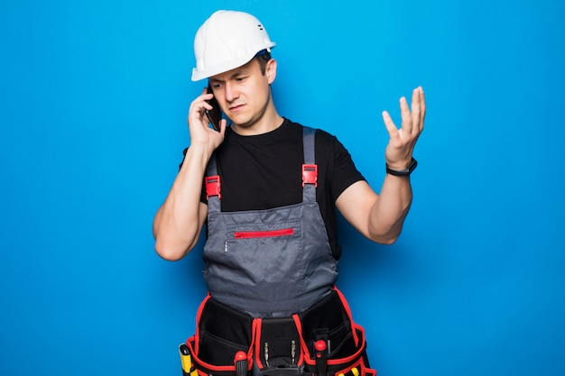 Young workman with helmet making phone call and speaking with someone on blue background