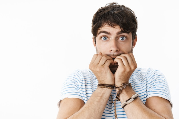 神経質に爪を噛むウェーブのかかった髪の若い心配している魅力的な男は、誰かが心配して立っている汚い秘密を知っているので、青い目を広げます。