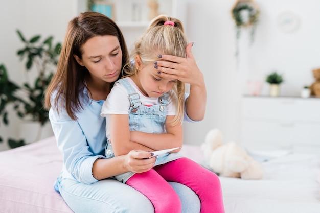 温度計を見ながら病気の娘の額に触れる若い心配ブルネット女性