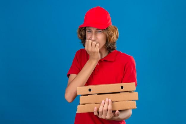 孤立した青い背景に爪をかむ口に手でストレスと緊張を探している赤い制服を保持している若い心配して配達人