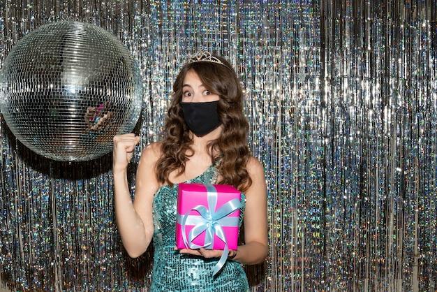 Giovane donna graziosa preoccupata emotiva preoccupata che indossa un abito lucido con paillettes con corona nella mascherina medica nera e tenendo un regalo nel partito