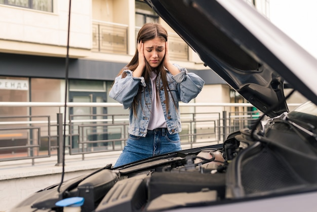 La giovane ragazza preoccupata sta usando un telefono per spiegare al meccanico il problema con un'auto che ha.