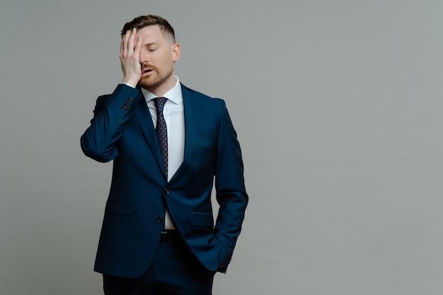 공식적인 마모에 젊은 걱정 남자 관리자는 비즈니스 실패에 대해 좌절감을 느끼고 화가 나서 얼굴에 손을 잡고 회색 배경에 서있는 동안 눈을 감고 텍스트 복사 공간