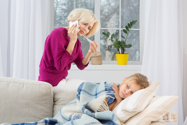Young worried mom calling doctor measuring temperature of her daughter.