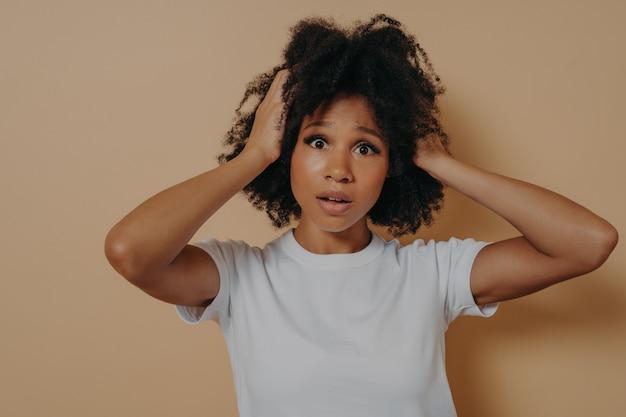 Молодая взволнованная африканская женщина с открытым ртом, держащая голову руками и смотрящая в камеру с шокированным и расстроенным выражением лица, слышит плохие негативные новости или имеет проблемы / проблемы