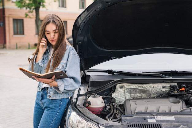 車の避難を呼びかけている心配している若い女性が道路で故障した。女性は故障した車の保険サービスを呼び出します。