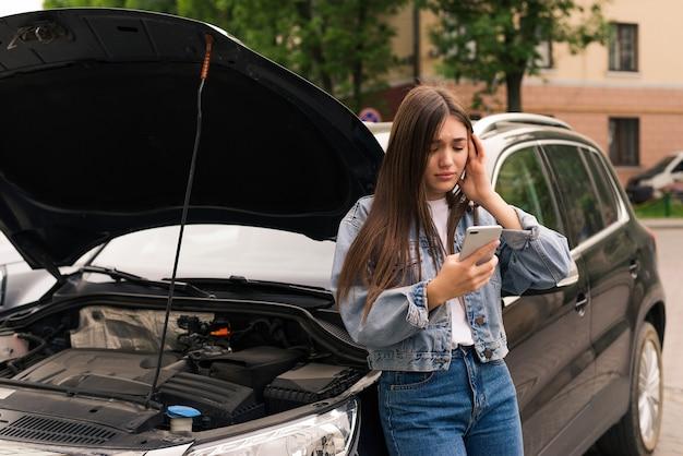 車の避難を呼びかけている心配している若い女性が道路で故障した。