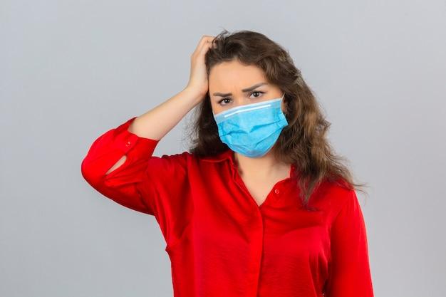 Giovane donna preoccupata che indossa camicetta rossa in maschera protettiva medica toccando la testa sentirsi depressi su sfondo bianco isolato