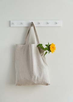 Young yellow sunflower in textile eco bag hanging