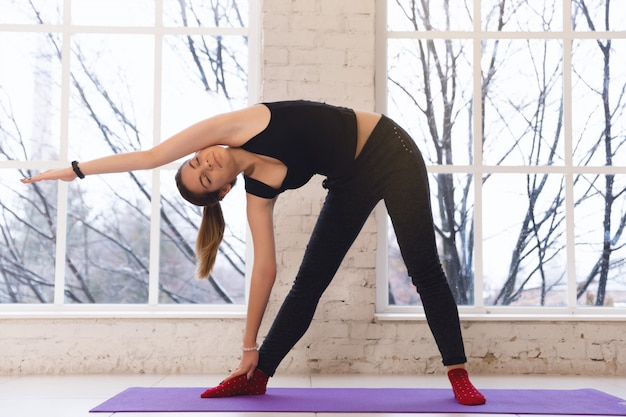 Young yoga girl warming up doing side tilt in a bright room inside the room opposite the window