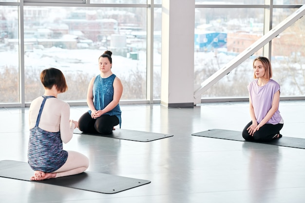 体育の開始前に前のマットに座っているアクティブな女性に推奨を与える若いヨガトレーナー