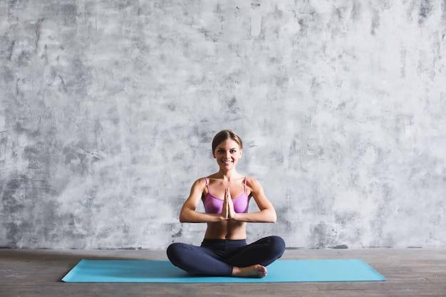 Молодая женщина йоги в положении молитвы в помещении.