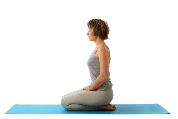 Young yoga woman in the virasana position. isolated on white wall