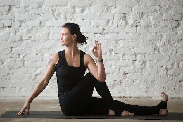 Giovane donna attraente yogi in ardha matsyendrasana posa, bianco