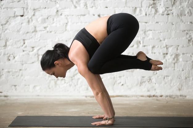 Young yogi attractive woman in bakasana pose, white loft backgro