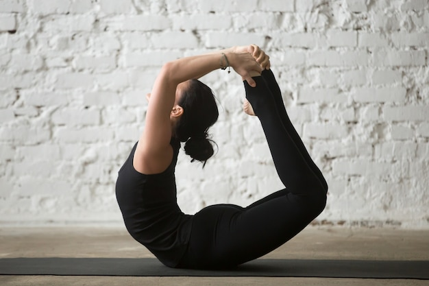 Young yogi attractive woman in bow pose, white loft background
