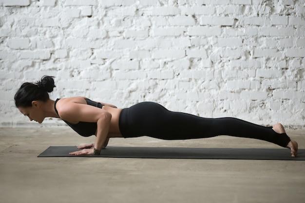 Giovane donna yogi attraente in chaturanga dandasana pose, loft b