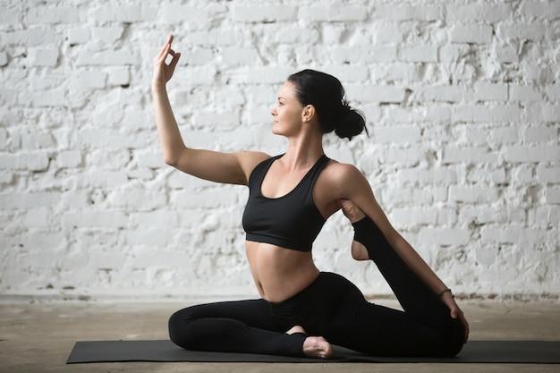 Young yogi attractive woman doing one legged king pigeon pose