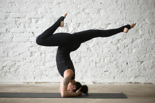 Young yogi attractive woman doing supported headstand pose varia