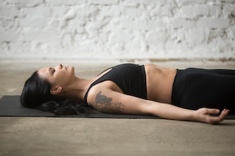 Young yogi attractive woman in Savasana pose, loft background, c