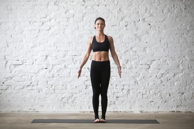 Young yogi attractive woman in mountain pose, white loft backgro