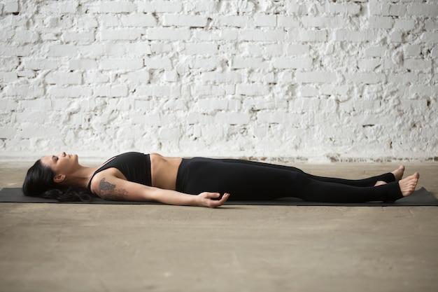 Young yogi attractive woman in savasana pose, white loft backgro