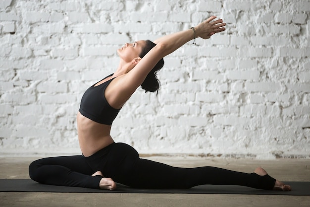 Young yogi attractive woman in single pigeon pose, loft backgrou