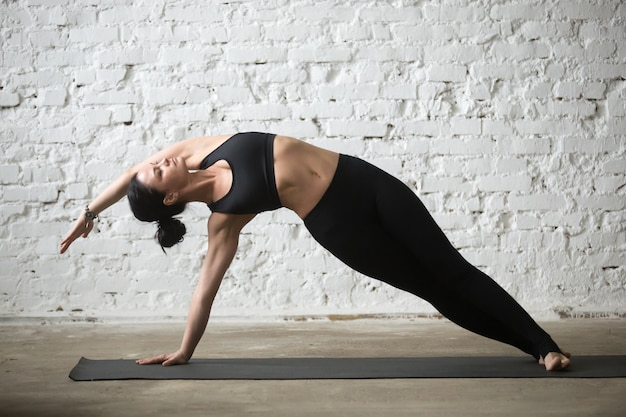 Young yogi attractive woman in vasisthasana pose, white loft bac