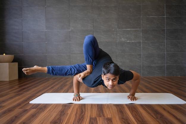 Young yogi doing astavakrasana exercise in gym
