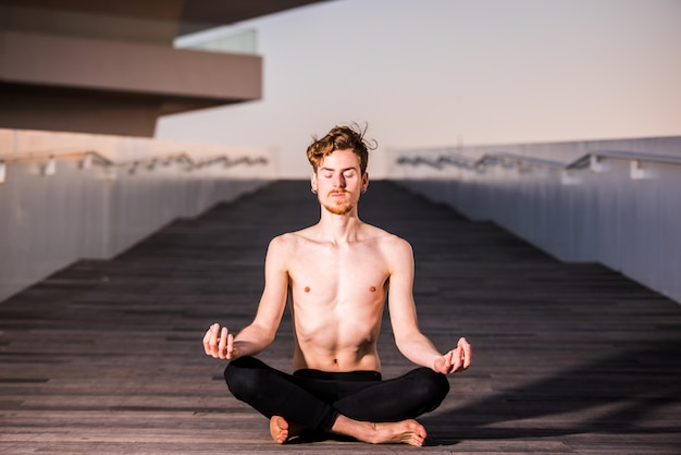 A young yogi places his relaxed hands on his knees during the lotus asana, sitting on wood. copy space