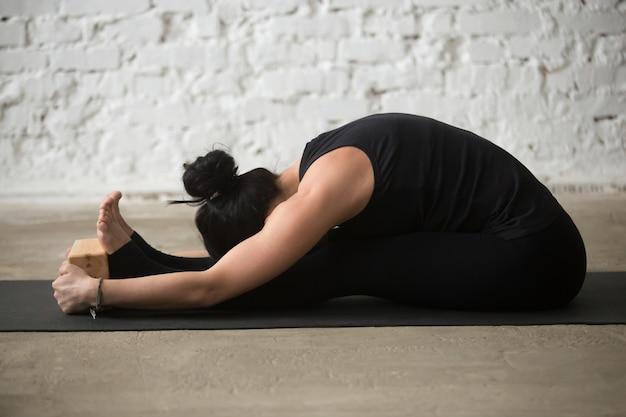 Young yogi woman in paschimottanasana pose with block, loft back