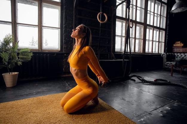 Молодая женщина йоги, практикующая концепцию йоги, делает упражнения на одноногих королевских голубях, тренируется в спортивной одежде на лофт-студии
