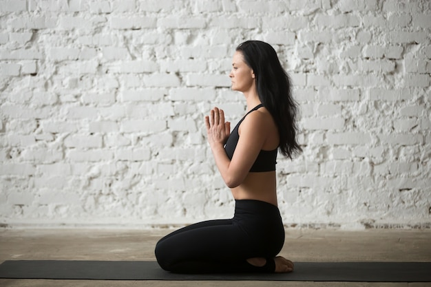 Young yogi woman in seiza pose with namaste, loft background