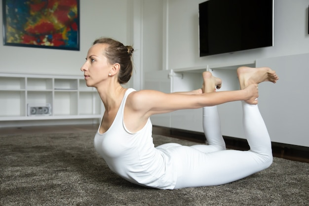 Young yogi woman stretching in bow exercise