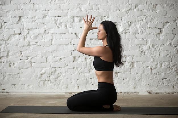 Young yogi woman in vajrasana pose with namaste, loft background