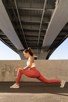Young yogi woman working out outdoor under bridge