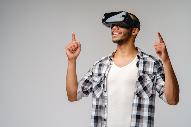 Young young man wearing vr virtual reality headset over light grey wall
