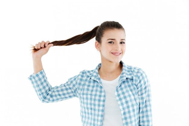 Молодая молодая женщина играет со своими волосами