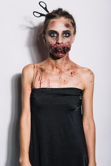 Young zombie in black dress