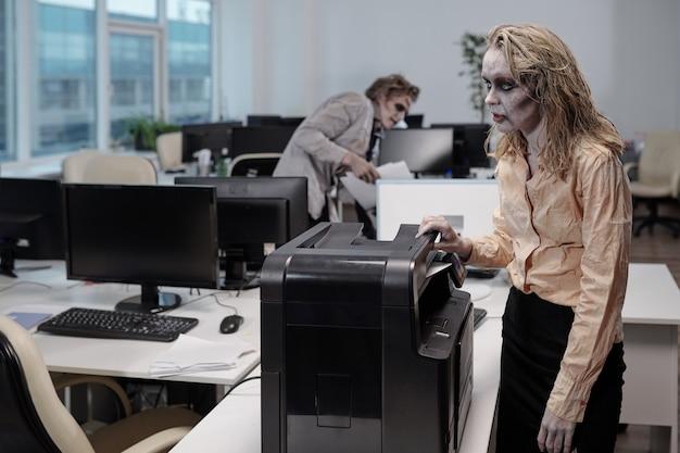 Молодая женщина-зомби стоит у ксерокса и делает копии документов против мертвого коллеги-мужчины с бумагами