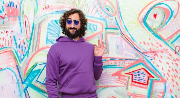 Young慢、成功、肯定的で誇りに思って、落書きの壁に自己を指している若いひげを生やした狂気の男