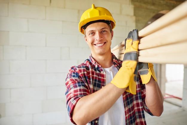若い大工は木の板を持っています