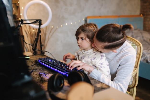 妹は兄弟の膝の上に座って、ネオンライトの小さな女の子の助けを借りてキーボードに指を置きます