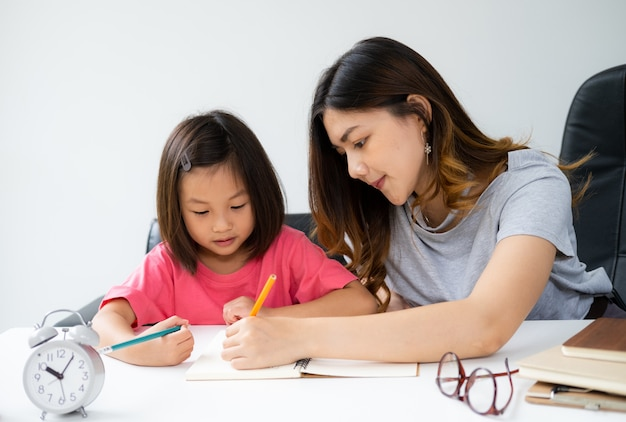 Younger woman teaches homework to her kid at home