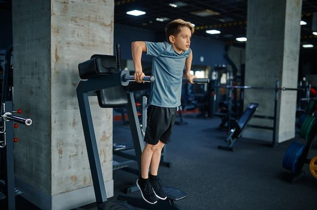 체육관에서 컴퓨터에 abs 운동을하는 젊은이. 스포츠 클럽, 건강 관리 및 건강한 라이프 스타일, 운동에 모범생에서 체력 훈련에 소년
