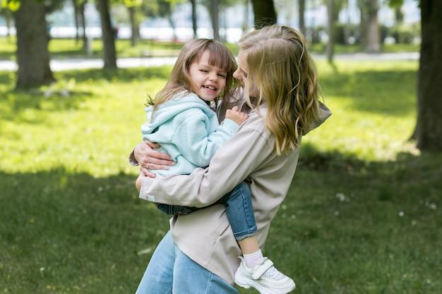 屋外の若者とママを抱いて